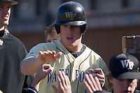 Allan Dykstra (10) of the Wake Forest Demon Deacons high fives teammates after scoring a run versus the Clemson Tigers during the second game of a double header at Gene Hooks Stadium in Winston-Salem, NC, Sunday, March 9, 2008.