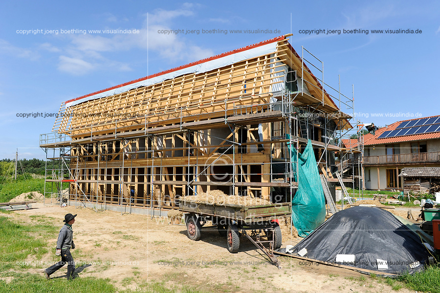 GERMANY, eco village Siebenlinden, construction site of building with straw bale and clay, behind straw bale house with sun collectors on the roof / DEUTSCHLAND, Oekosiedlung Siebenlinden in der Altmark, Baustelle eines neuen Wohnhaus aus einer Holzkonstruktion mit Strohballen , Hintergrund fertiges Strohballenhaus mit Lehm verputzter Wand und Solarkollektoren auf dem Dach - Bürgerenergie, Buergerenergie