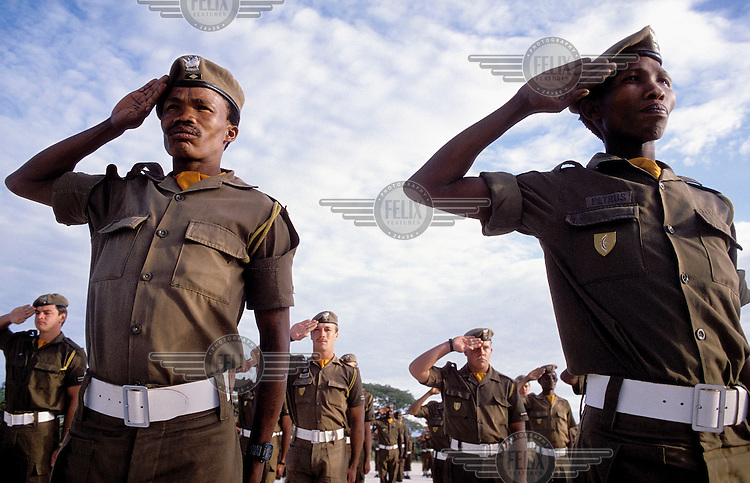 Soldiers at an army camp salute while on parade.
