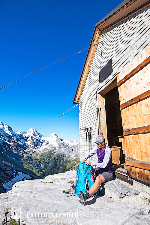 A woman hiker sitting outside the Silberhornhütte, Jungfrau Region, Switzerland