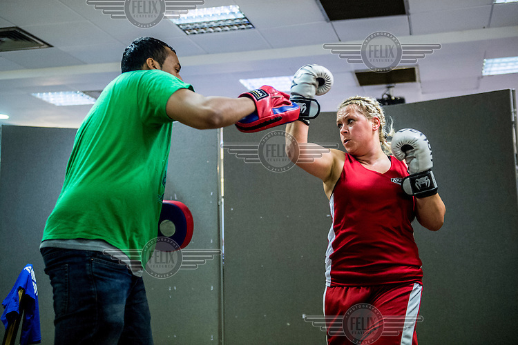 A female boxer prepares for a fight with her trainer at the London Irish Centre where the 'Carpe Diem' white collar boxing event is taking place. <br /> <br /> 'White-collar boxing' is a growing phenomenon amongst well paid office workers and professionals and has seen particular growth in financial centres like London, Hong Kong and Shanghai. It started at a blue-collar gym in Brooklyn in 1988 with a bout between an attorney and an academic and has since spread all over the world. The sport is not regulated by any professional body in the United Kingdom and is therefore potentially dangerous, as was proven by the death of a 32-year-old white-collar boxer at an event in Nottingham in June 2014. The London Irish Centre, amongst other venues, hosts a regular bout called 'Carpe Diem'. At most bouts participants fight to win. Once boxers have completed a few bouts they can participate in 'title fights' where they compete for a replica 'belt'.