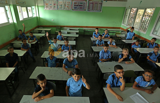 Palestinian schoolchildren sit inside their classrooms on the first day of a new school year, at a United Nations-run school in Deir al-Balah refugee camp in the central Gaza Strip August 23, 2017. Photo by Ashraf Amra