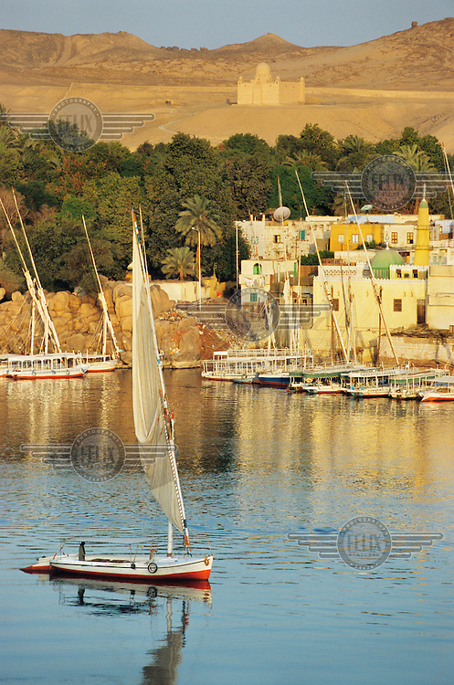 A felucca, a traditional wooden sailing boat, passes the city of Aswan on the River Nile at the edge of the Western Desert..