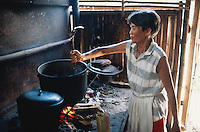 Philippines. Negros Island. Province of Negros Occidental, located in the  Western Visayas region. Barangay (village) Camao. An old woman cooks food on a fire stove.  © 1999 Didier Ruef