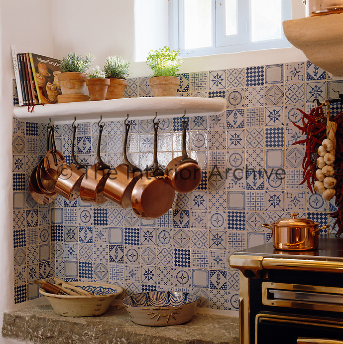 A collection of polished copper pans hangs below a shelf of herbs planted in small terracotta pots