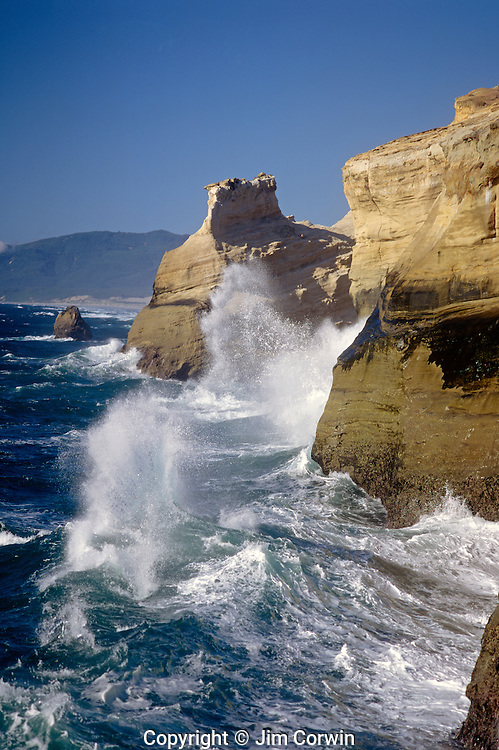 Cape Kiwanda State Park National Recreation Area big waves breaking onto rocky cliffs afternoon with blue skies Northern Oregon Coast Oregon State USA