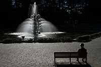 An old man sits on park bench by a fountain in Setagaya Park, Tokyo, Japan. Thursday November 21st 2019
