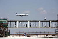 Workers operate on an airport terminal of the Pudong Airport expansion project while a plane approaches to land in Shanghai, China..