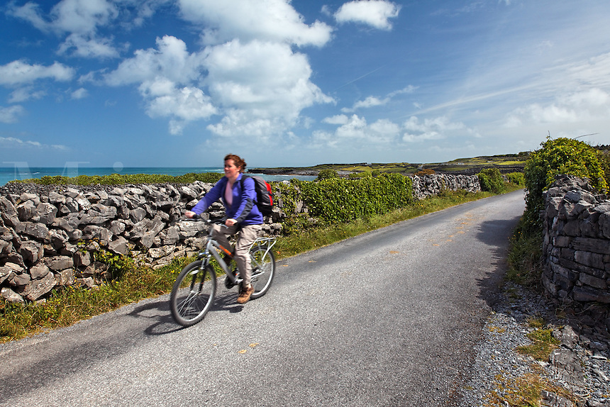 Woman riding bicycle on stone wall lined road on the island of Inishmore, Aran Islands, County Galway, Republic of Ireland