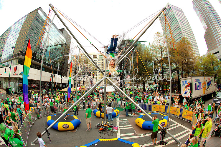 Photography of the Charlotte NC St. Patrick's Day Parade in March 2012. Image shows people having fun bungee jumping near the parade route. Photography is part of a series of St. Patrick's Day Parade photos in Charlotte, NC.