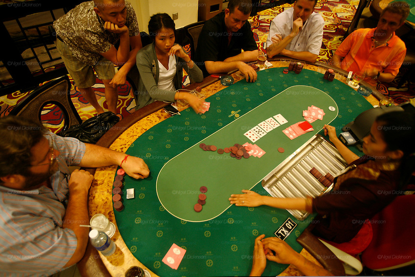 Phnom Penh's Nagaworld Casino and five-star hotel is one of Cambodia's biggest private employers with more than 3,000 staff catering for a stream of visitors. It functions non-stop 24 hours a day with an inside airconditioned controlled temperature of 21 degrees.It is a 14 storey hotel and entertainment complex, with more than 500 bedrooms, 14 restaurants and bars, 700 slot machines and 200 gambling tables. There is also a spa, karaoke and VIP suites, live bands, and a nightclub. Its monolithic building dominates the skyline at the meeting point of the Mekong and Tonle Sap rivers, in stark contrast to nearby intricate Khmer architecture.///Western gamblers playing poker at Nagaworld