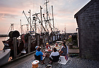 Eating seafood at sunset on the pier in fishing port of Menemsha in Chilmark, on the Massachusetts islands of Martha's Vineyard. ..