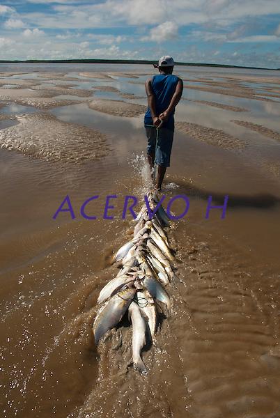 Pescadores artesanais preparam as fieiras com os peixes capturados para transporta-los at&eacute; o barco, ap&oacute;s um dia de trabalho. A pesca realizada na Reserva Extrativista Marinha M&atilde;e Grande no litoral do Par&aacute;, na foz do rio Amazonas, rende aos pescadores por dia cerca de 200 quilos de pescado de v&aacute;rias esp&eacute;cies como: piramutabas, sardinhas, filhotes, pescada amarela, robalo e tainhas.<br /> Curu&ccedil;&aacute;, Par&aacute;, Brasil.<br />  Foto: Paulo Santos <br /> 20/05/2009