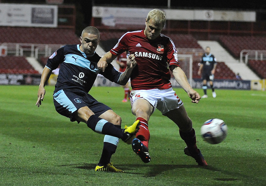 Burnley's Danny Lafferty whips the ball into the box while under pressure from Swindon Town's James McEveley ..Football - Capital One Cup Third Round - Swindon Town v Burnley - Tuesday 25th September 2012 - The County Ground - Swindon. .