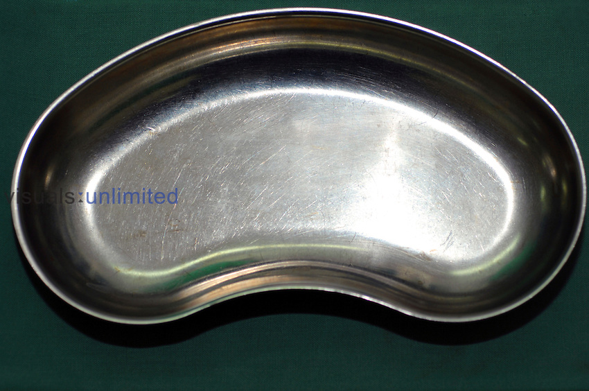 A stainless steel kidney dish is a bowl used in medical and surgical wards to receive soiled dressings and other medical waste. The shape of the dish allows it to be held against the patient's body to catch any falling fluids or debris. Royalty Free