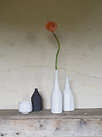 Still life of four objects including two bottle-shaped white vases, one shorter, black vase and a round, white bowl. One white vase has a single, orange flower, that has a stem equal in height to the vase. All four objects sit on wooden surface in front of a cracked beige wall.