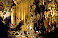 Groups of visitors admire the intricate patterns created by enormous stalagmites and stalactites extending from the roof and floor of the famous Luray Caverns. Luray Virginia, Luray Caverns.