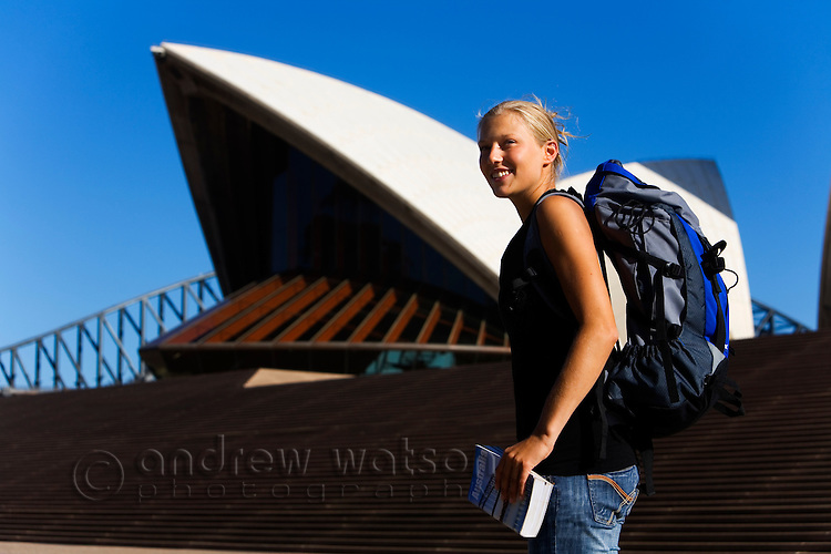 A backpacker with guidebook in front of the Sydney Opera House.  Sydney, New South Wales, AUSTRALIA.