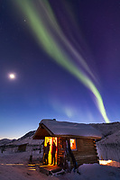 Visitors to the Caribou bluff cabin in the White Mountains National Recreation area view the northern lights overhead on a winter night.