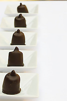 Detail of a line of pralines with pistachio and orange by Corrado Assenza