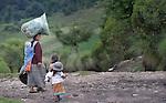 A woman walks along a road with her children in San Jose la Frontera, a small Mam-speaking Maya village in Comitancillo, Guatemala.
