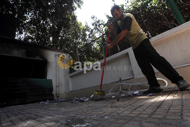 Egyptian Men remove the damages in the burnt campaign headquarters of candidate and former prime minister Ahmed Shafiq in Cairo May 29, 2012. A group of Egyptian protesters set fire to the headquarters on Monday, the state news agency reported, after the ex-prime minister made it into the second round of the vote. Photo by Ashraf Amra