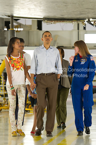 United States President Barack Obama holds hands with his daughter Malia as they walk under the space shuttle Atlantis during a tour the first family received of the the NASA Orbital Processing Facility given by Director of Flight Crew Operations for the Johnson Space Center and Astronaut, Janet Kavandi, right, at the NASA Kennedy Space Center in Cape Canaveral, Florida, Friday, April 29, 2011. .Mandatory Credit: Bill Ingalls / NASA via CNP