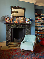 A Victorian button-backed armchair in the blue living room beside the marbleised fireplace