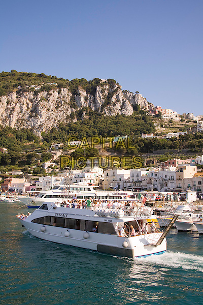 View of harbour, cruise boat, buildings and mountains, Marina Grande, Capri, Italy
