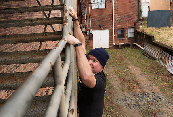 December 22, 2014. Lexington, North Carolina.<br />  Mayor Newell Clark uses a factory staircase as part of his exercise routine with local citizens.<br />   Newell Clark, the 43 year old mayor of Lexington, NC, leads a group of friends and colleagues on a 4 times a week exercise routine around downtown. The group uses existing infrastructure, such as an abandoned furniture factory, loading docks, stairs, and handrails to get fit and increase awareness of healthy lifestyles in a town more known for BBQ.<br /> Jeremy M. Lange for the Wall Street Journal<br /> Workout_Clark