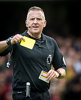 Referee Jonathan Moss displays a yellow card during the Premier League match between Chelsea and Watford at Stamford Bridge, London, England on 21 October 2017. Photo by Andy Rowland.