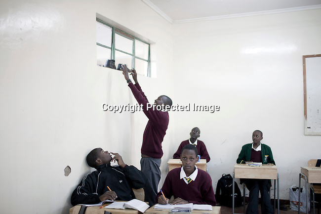 ELDORET, KENYA - MAY 19: Eliud Kibet, age 18, changes to school shoes from running shoes in his class room at Kipkeino Highschool. He is promising long distance runner and he has already trained for an hour from 5.15 in the morning. (Photo by: Per-Anders Pettersson)