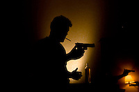 """San Francisco State student Andrew Prine loads an non-nethal plastic ball """"airsoft"""" pistol for target practice inside a hotel room in Downtown Pasadena Thursday evening Nov. 2, 2007. ."""