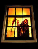 Magere Hein voor het raam tijdens halloween