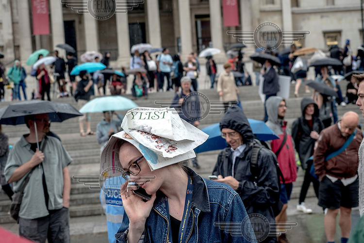 A women uses a newspaper to shelter from the rain during a rally in Trafalgar Square at which tens of thousands of people protested the outcome of the EU referendum and declared their support for the EU.