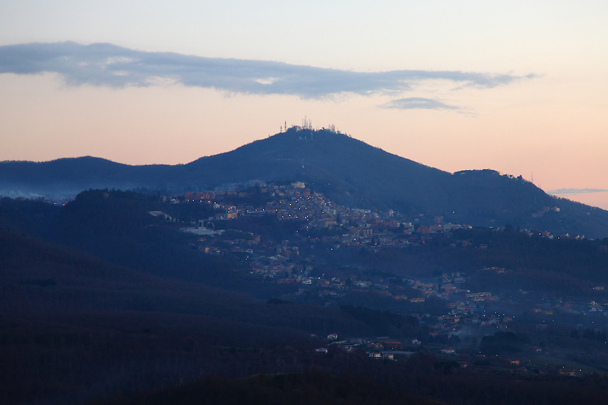 Tuscolo: The view from the archeological park in the late afternoon, onto the facing small town with some lights already turned on, the typical hill on the background with its antennas on the top, and some clouds. Digitally Improved Photo.