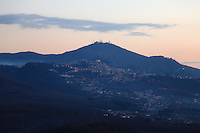 Tuscolo (near Monte Compatri): The view from the archeological park in the late afternoon, onto the facing small town of Molara, with some lights already turned on, the typical hill on the background with its antennas on the top, and some clouds.<br />