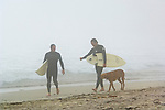 Two surfer men holding surfboards walking on sand in fog at Pfeiffer Beach, Big Sur Coast, Monterey County, California