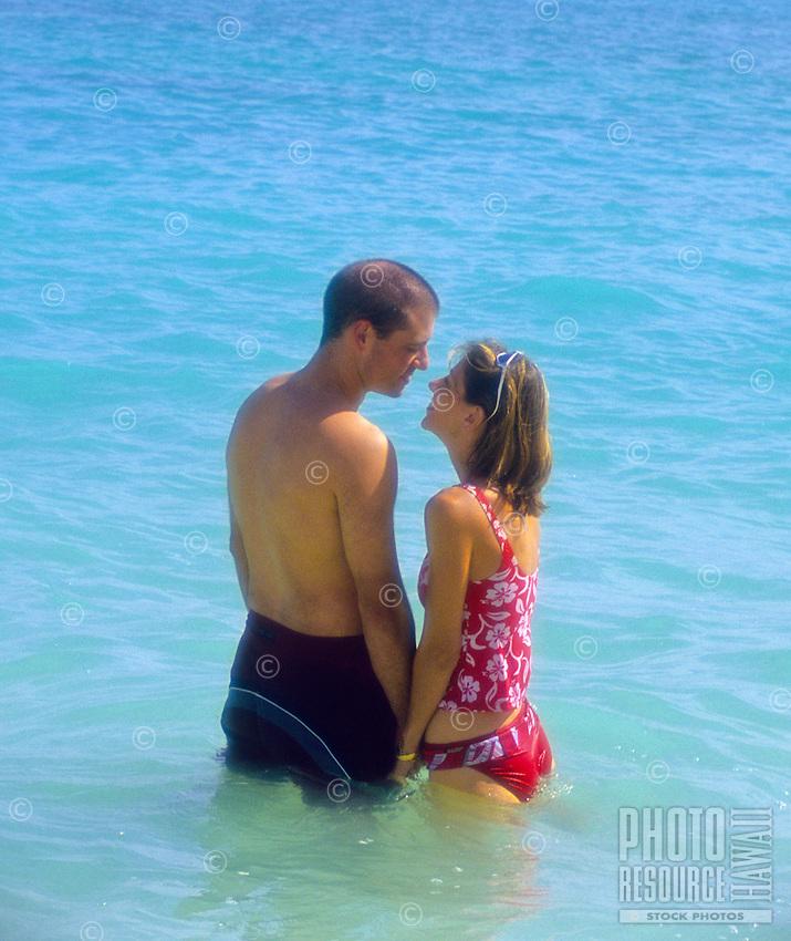 A romantic couple enjoys the refreshing water and warm sun at Lanikai Beach near Kailua, on Oahu's Windward side.