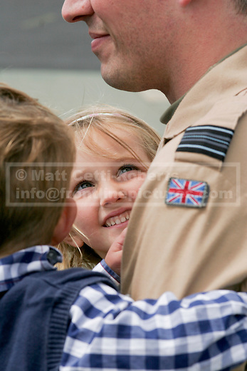 A young girl looks up at her father, an RAF squadron leader, newly returned from Iraq. The return of his squadron marked the end of almost two decades of RAF operations in the Middle East that began with the 1991 Gulf War.