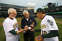 OAKLAND, CA - AUGUST 14:  Photographer Doug McWilliams and Oakland Athletics team photographer Michael Zagaris get a baseball signed by A's broadcaster Ray Fosse after they threw out a ceremonial first pitch before the game between the Kansas City Royals and Oakland Athletics at the Oakland Coliseum on Monday, August 14, 2017 in Oakland, California. (Photo by Brad Mangin)