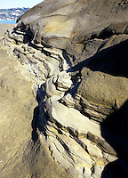 WATER EROSION on sandstone cliffs<br /> Stratified rock, a layered sedimentary rock, deposit with water erosion.