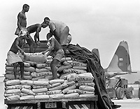 Kenyan workers load a truck to move bags of corn soya milk powder to a military cargo plane in Mombasa, Kenya for the flight to a Somali refugee camp in the Kenyan countryside. Joint Task Force Provide Relief airlifted food and supplies to refugee centers where Somalis fled to excape civil war in their homeland. The multinational airlift operation was a part U.N. Operation Restore Hope in 1992-93