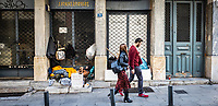 Pictured: A young couple walk past a homeless man.<br /> Re: Street photography, Athens, Greece. Thursday 27 February 2020