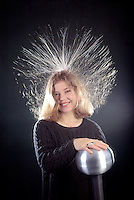 VAN DE GRAAFF GENERATOR: HAIR STANDING ON END<br /> (Variations Available)<br /> Electrical Conduction<br /> A comb of corona points charges a spinning belt. Another comb removes the charge and conducts it to the outside conducting shell where the static charge can reach millions of volts. The charge then travels through the girl's body.