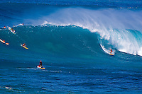 Surfer riding huge winter surf at Waimea Bay, on the North Shore of Oahu