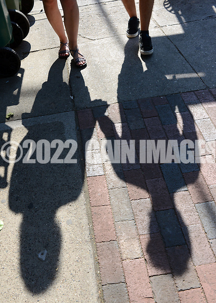NEW HOPE, PA - JUNE 02: Debbie Morrison, 31, of Seargentsville, New Jersey and Miguel Santana, 23, of Spain walk together as their shadows cast as they hold hands on a warm afternoon June 2, 2014 in New Hope, Pennsylvania.  The temperature reached 82 degrees in New Hope and is expected to remain in the mid-80's for the next few days. (Photo by William Thomas Cain/Cain Images)