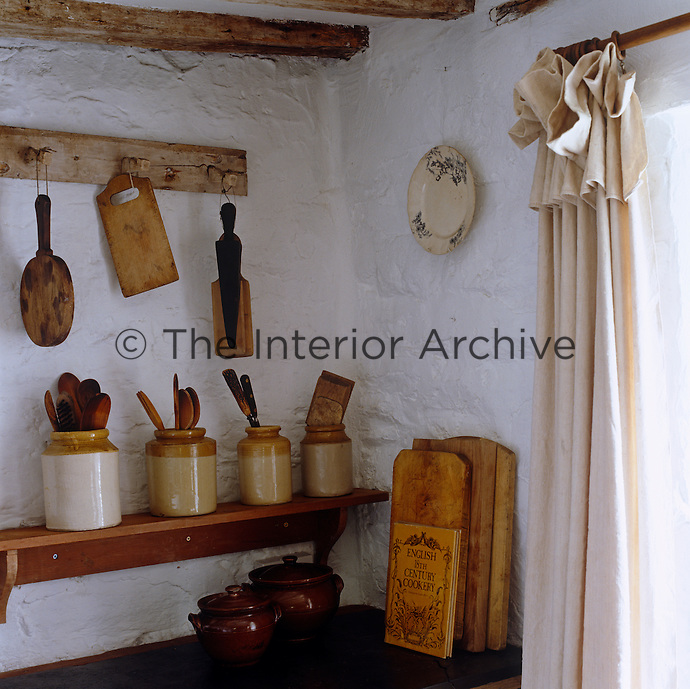 A series of earthenware storage jars house the wooden kitchen utensils in a corner of the rustic kitchen