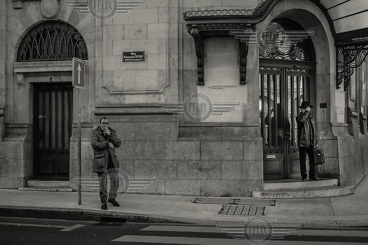 A man leaves the Societe Generale Private banking building while a man smokes a cigarette in the street outside.