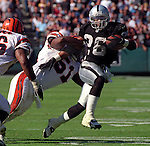 Oakland Raiders vs. Cincinnati Bengals at Oakland Alameda County Coliseum Sunday, October 25, 1998.  Raiders beat Bengals 27-10.  Cincinnati Bengals linebacker Takeo Spikes (51) tackles Oakland Raiders running back Napoleon Kaufman (26).